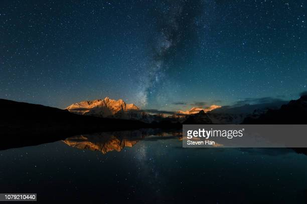 the milky way hanging over snow mountains with the moon rising - tibetaanse cultuur stockfoto's en -beelden