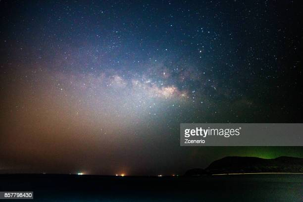 The milky way lies across dark sky in a space universe with sea and mountains view
