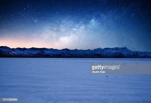 the milky way over the snow mountains of tibet - stimmungsvoller himmel stock-fotos und bilder