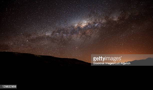 The Milky Way setting behind the hills of Azul, Argentina, part of the Tandilia Hills. The light dome of the city of azul glows above the hills.