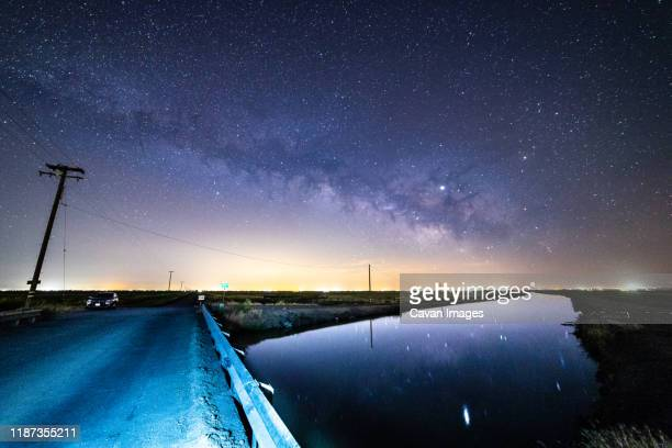 the milky way stretching across sky above road bridge in remote town. - マーセド郡 ストックフォトと画像
