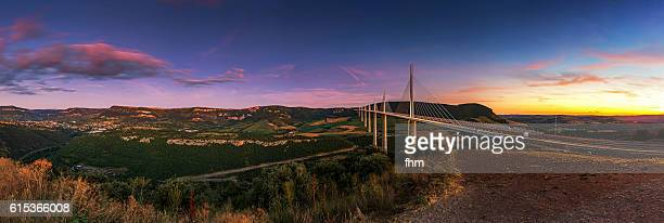 The Millau Viaduct (French: le Viaduc de Millau) - Panorama with Millau town at colorful sunset
