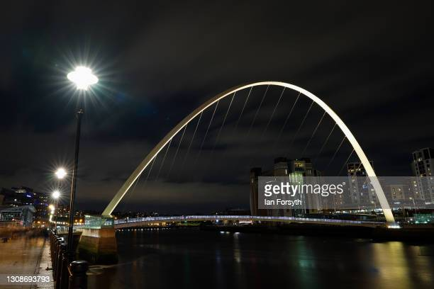 The Millennium bridge across the River Tyne is illuminated yellow during a National Day of Reflection on March 23, 2021 in Newcastle Upon Tyne,...
