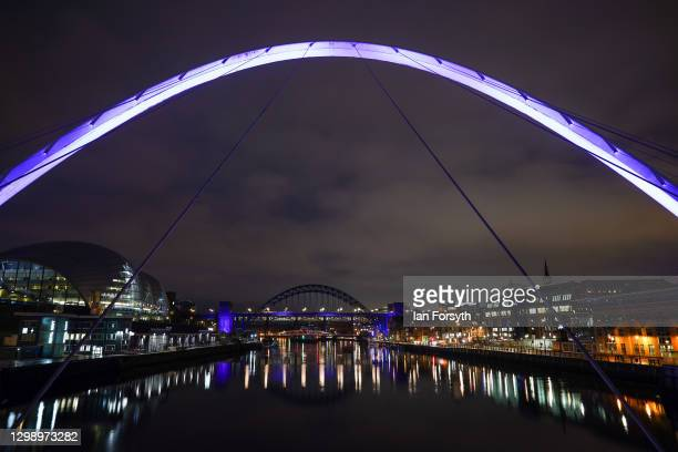 The Millennium Bridge and beyond it the Tyne Bridge in Newcastle are bathed in purple light to commemorate Holocaust Memorial Day on January 27, 2021...