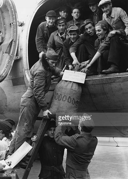 The millionth bag of coal to be delivered during the Berlin Airlift handed down from a US Skymaster to pilot Sergeant Clyde Peterson and Group...