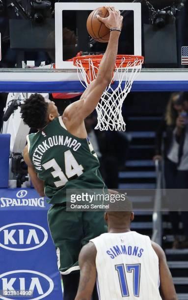 The Milwaukee Bucks' Giannis Antetokounmpo dunks over the Orlando Magic's Jonathon Simmons at the Amway Center in Orlando Fla on Wednesday March 14...