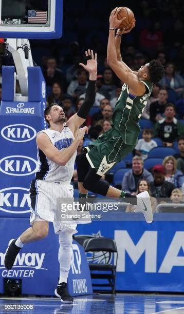 The Milwaukee Bucks' Giannis Antetokounmpo right shoots over the Orlando Magic's Nikola Vucevic at the Amway Center in Orlando Fla on Wednesday March...