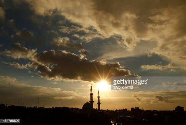 The minaret of a mosque is silhouetted at sunset in the southern Gaza Strip town of Rafah on the border with Egypt on December 10 2013 AFP PHOTO/...