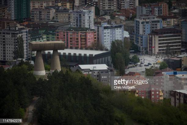 The Miners Monument is seen on a hilltop in the majority ethnicSerb north as people walk under the flag of the Republic of Kosova in a square in the...