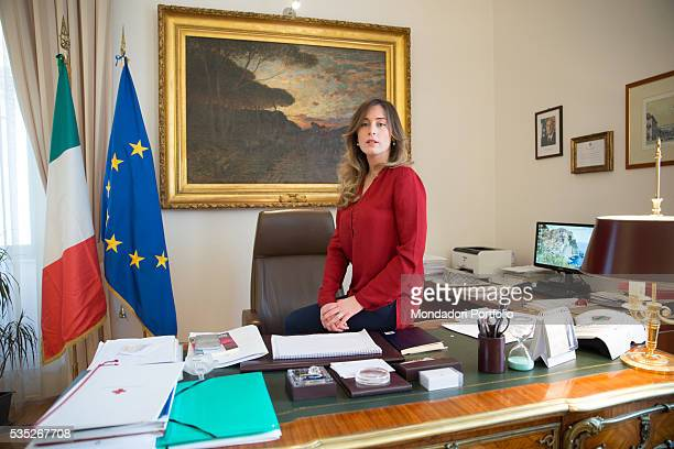 The Minister of Constitutional Reforms and Relations with Parliament of the Italian Republic Maria Elena Boschi sitting on the desk in her office...
