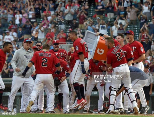 The Minnesota Twins celebrate as Brian Dozier of the Minnesota Twins crosses home plate after a walkoff grand slam against the Tampa Bay Rays during...