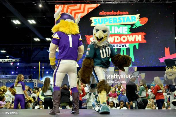 The Minnesota Vikings and Philadelphia Eagles mascots are seen onstage before the JoJo Siwa performs at Nickelodeon at the Super Bowl Expereince...