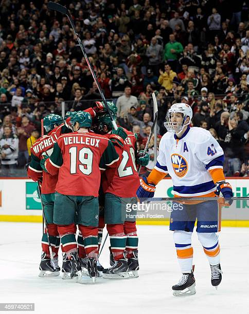 The Minnesota Wild celebrate a goal by Ryan Suter of the Minnesota Wild as Andrew MacDonald of the New York Islanders looks on during the first...
