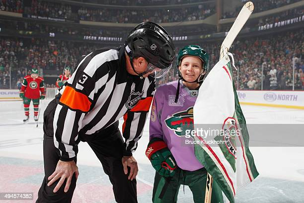 The Minnesota Wild flag bearer wears a lavender jersey for Hockey Fights Cancer Awareness Night while talking to referee Mike Leggo prior to the game...