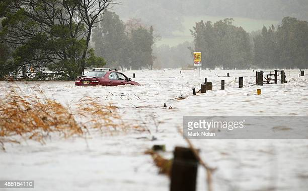 The Minumurra River floods farm land and a car is stranded on August 25 2015 in Jamberoo Australia Residents downstreamm of the Jerra dam which feeds...