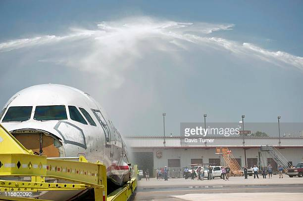 The Miracle on the Hudson plane is hauled under ceremonial sprays of water as it enters the tarmac of the Charlotte Douglas Airport June 10 2011 in...