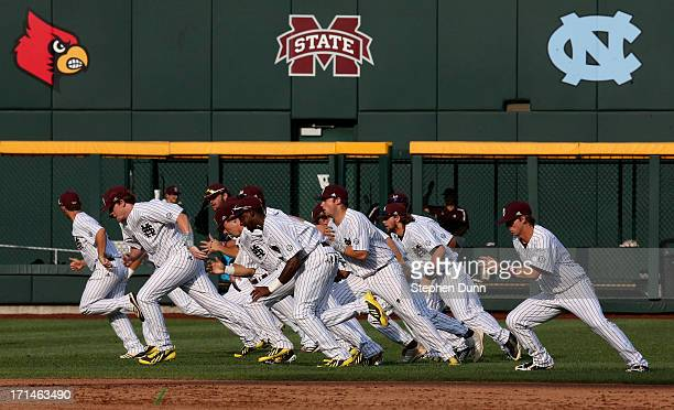 The Mississippi State Bulldogs run in the outfield to warm up before playing the UCLA Bruins during game one of the College World Series Finals on...