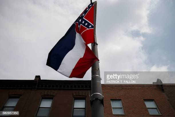 The Mississippi state flag which features the Confederate flag hangs as protestors gathered for a sit in demanding its removal during a protest at...