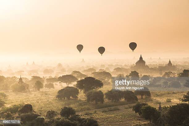 CONTENT] The misty landscape of The Bagan Archaeological Zone with silhouttes of hot air balloon and ancient temples at sunrise Old Bagan Mandalay...