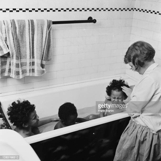 The mixed race Long family of Olyffe Avenue in Welling, Kent, July 1960. Twelve-year-old Joan helps bath her adopted twin sisters Mitch and Frankie,...