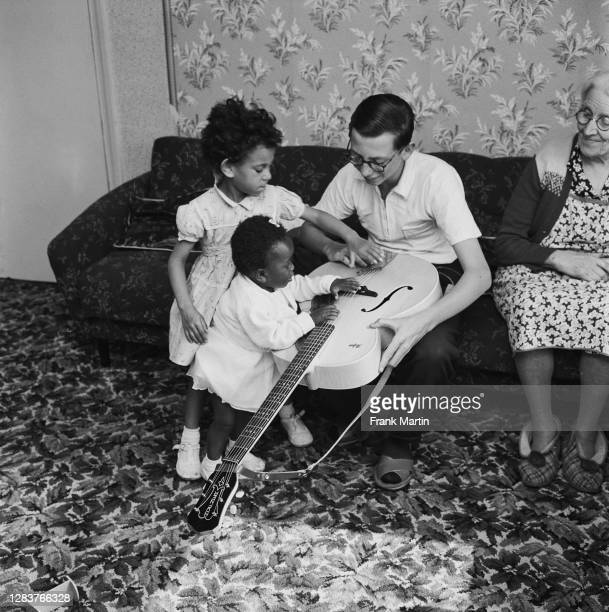 The mixed race Long family of Olyffe Avenue in Welling, Kent, July 1960. 13-year-old Ian teaches guitar to his adopted sisters Frankie and baby Kim.