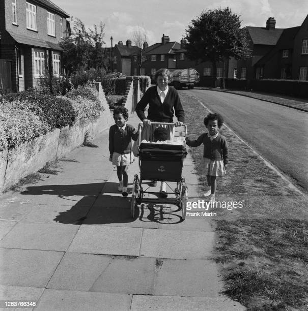 The mixed race Long family of Olyffe Avenue in Welling, Kent, July 1960. Twelve-year-old Joan goes for a walk with her adopted twin sisters Mitch and...