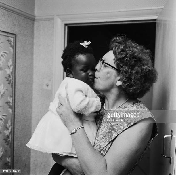 The mixed race Long family of Olyffe Avenue in Welling, Kent, July 1960. Mother Lydia Long kisses her newly-adopted daughter, baby Kim.