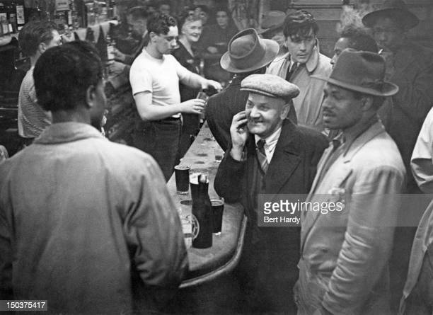 The mixed-race clientele of the Horns And Horse Shoe pub in Cable Street, Stepney, east London, June 1949. Original publication: Picture Post - 4825...