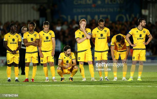 The MK Dons players nervously await the penalty deciding result during the Carabao Cup First Round match between AFC Wimbledon and Milton Keynes at...
