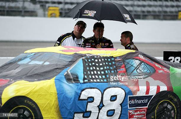 The M&M's car of David Gilliland, sits covered on pit road as rain falls prior to the NASCAR Nextel Cup Series Dodge Avenger 500 on May 12, 2007 at...