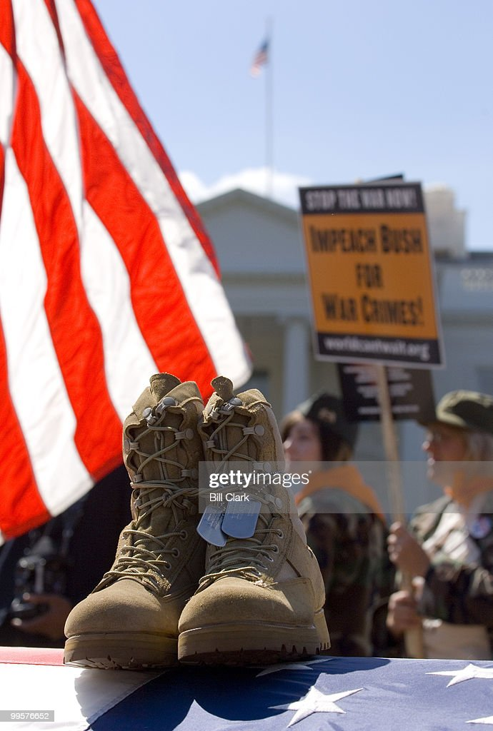 The mock flag-draped coffin and combat boots displayed in memory of Marine Lance Cpl. Alexander S. Arredondo,of Randolph, Mass., rests in the middle of Pennsylvania Avenue in front of the White House as anti-war protesters gather for the march to the Capitol on Saturday, Sept. 15, 2007.