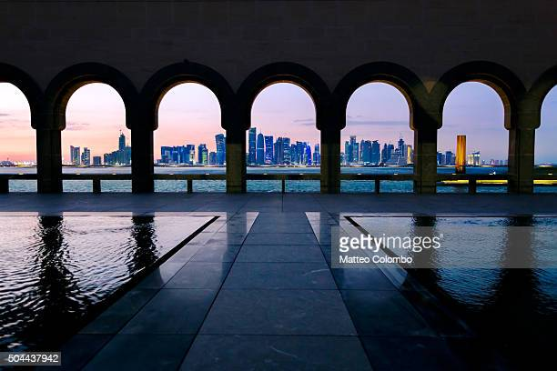 The modern city of Doha at sunset framed through archway, Qatar