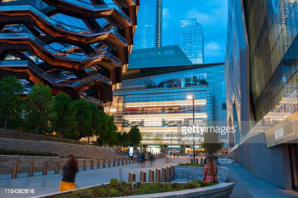 the modern new buildings at hudson yards with people walking or resting in midtown manhattan - hudson yards stock pictures, royalty-free photos & images