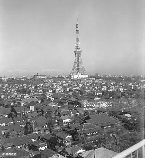The modern Tokyo Tower similar in design to the Eiffel Tower stands over a neighborhood of houses with traditionalstyled roofs in Tokyo Japan