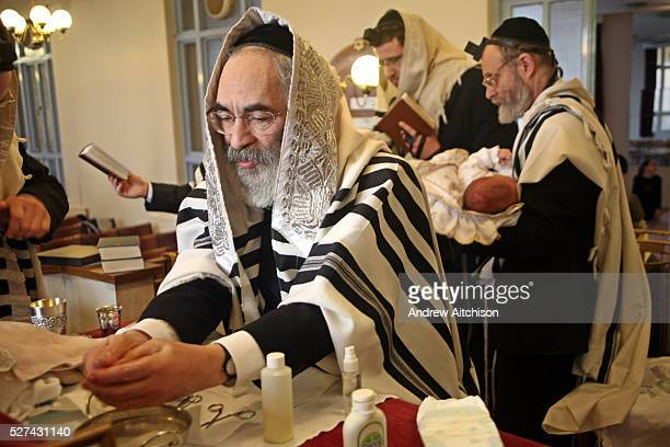 The Mohel washes his hands before the circumcision ceremony begins. On the 8th day after birth a Brit Milah is performed on a Jewish baby boy . The...