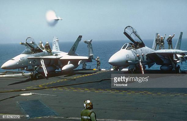 The moisture in the air around a Fighter Squadron 102 F14A Tomcat aircraft condenses into water vapor as the aircraft breaks the sound barrier while...