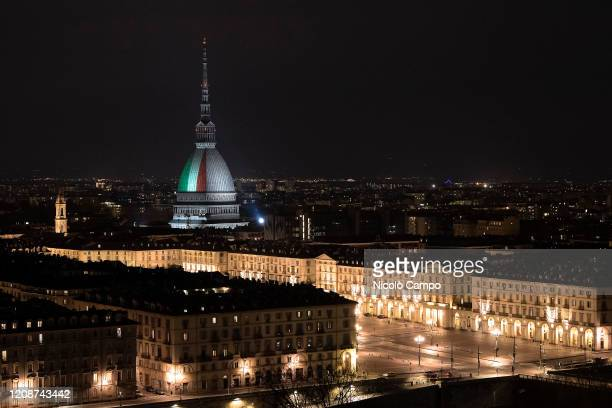 The Mole Antonelliana major landmark in Turin is illuminated with the colors of the Italian national flag to express solidarity and cohesion during...