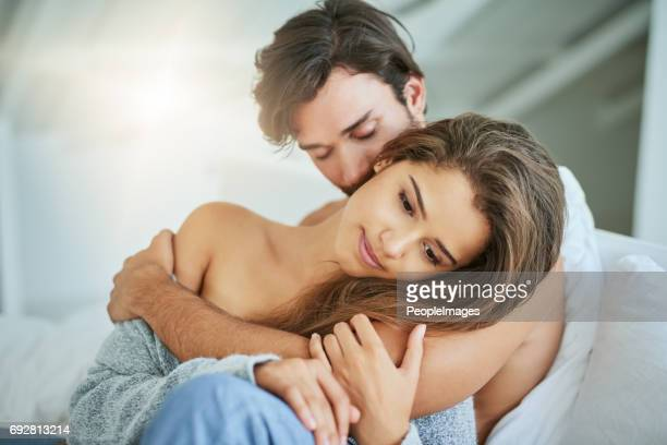 the moment she knew she wanted that feeling forever - couple cuddling in bed stock photos and pictures