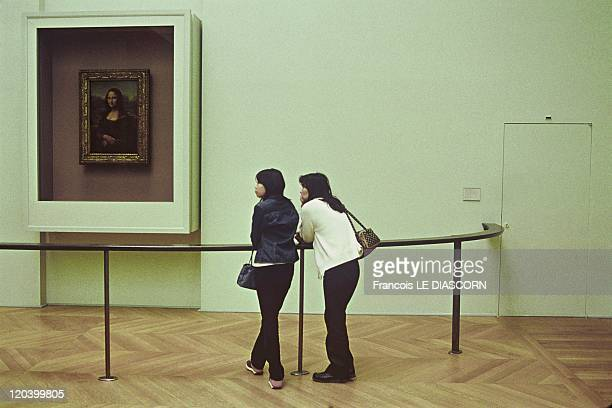 The Mona Lisa at the Louvre Museum in Paris France in October 2001 The Mona Lisa behind its bulletproof glass protection with two Japanese tourists...