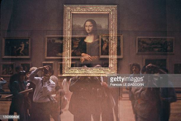 The Mona Lisa at the Louvre Museum in Paris France in October 2001 The Mona Lisa behind its bulletproof glass protection with Japanese tourists at...