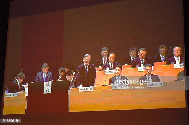 The monitor displaying Kansai Electric Power Co President Makoto Yagi stands up during the annual shareholders' meeting on June 28 2016 in Osaka...
