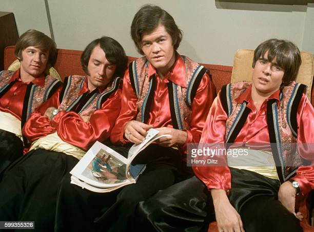 The Monkees relax on a couch between takes on their television show