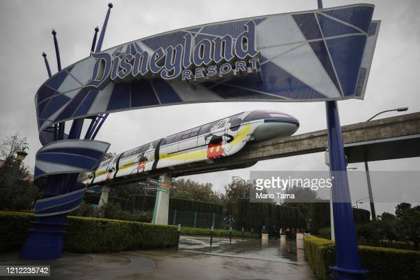 The monorail passes an entrance gate to the famed amusement park Disneyland on March 13, 2020 in Anaheim, California. Walt Disney Co. Is shuttering...