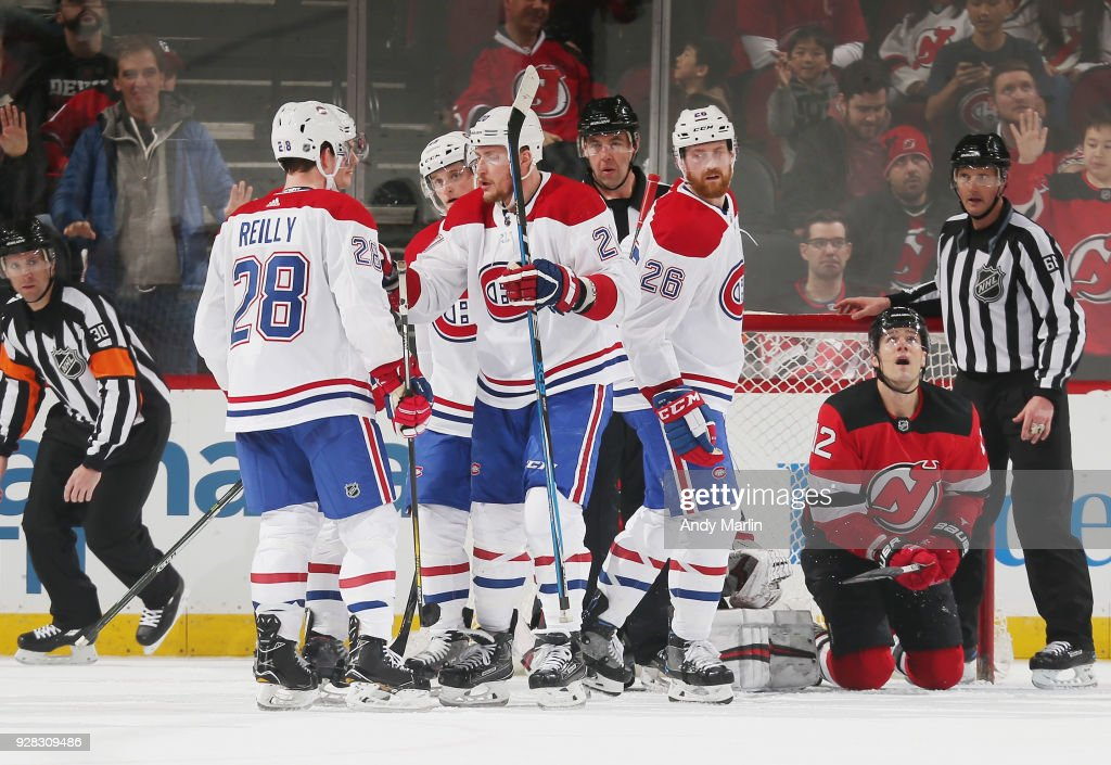 The Montreal Canadiens celebrate a goal by Byron Froese #42 (not pictured) as Ben Lovejoy #12 of the New Jersey Devils looks away duering the game at Prudential Center on March 6, 2018 in Newark, New Jersey.