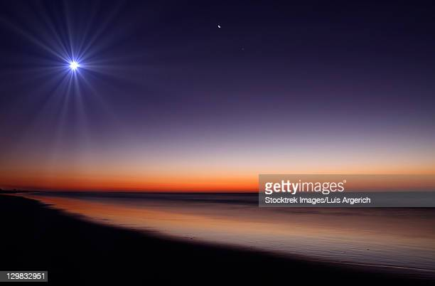 The Moon and Venus at twilight from the beach of Pinamar, Argentina.