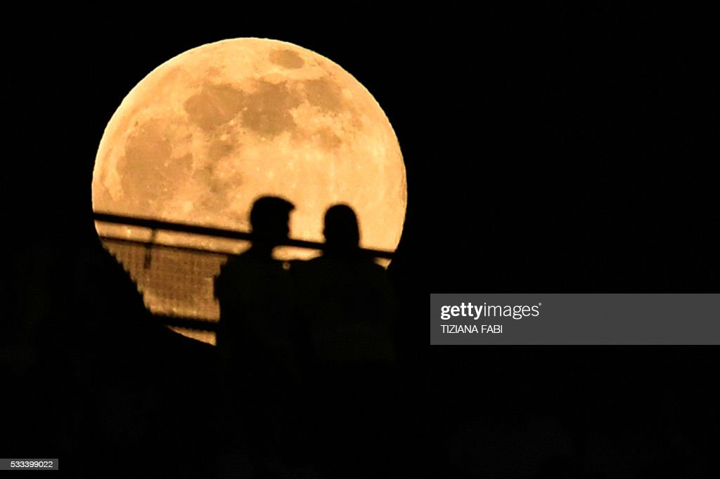 The moon appears behind the stands during the Italian Tim Cup final football match AC Milan vs Juventus on May 21, 2016 at the Olympic Stadium in Rome.