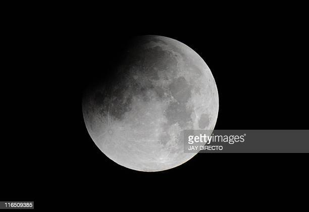 The moon is partially covered as a lunar eclipse gets underway as seen from the Philippine Observatory in Manila before dawn on June 16...