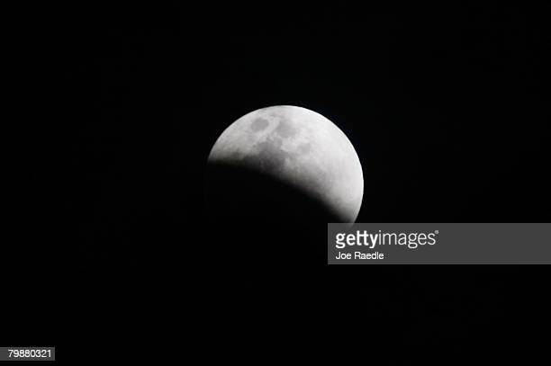 The moon is partly covered in the Earth's shadow during a phase of the lunar eclipse February 20 2008 in Miami Florida This will be the last lunar...