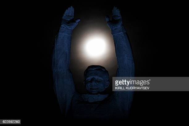 TOPSHOT The moon is pictured over a statue of the first Russian cosmonaut Yuri Gagarin at the Russian leased Baikonur cosmodrome early on November 12...