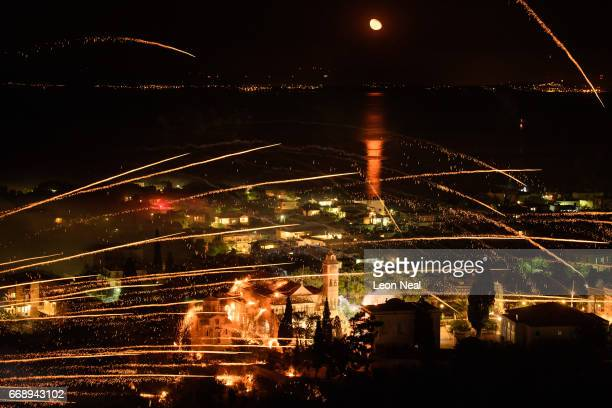The moon is reflected in the sea as rockets are fired between the Aghios Marko Church and the Panaghia Erithiani Church during the annual Rocket War...